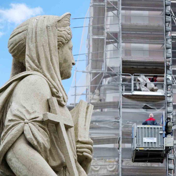 Voller Sorge beobachtet sie die Bauarbeiten am Turm der Stiftskirche.