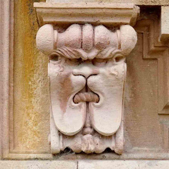 Ein grimmiges Löwengesicht mit gebundenem Maul an der Mauer der Certosa.