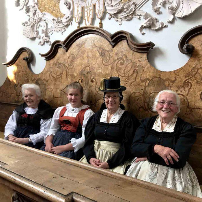 Die vier Damen haben in ihrer festlichen Sonntagstracht auf der Honoratiorinnenbank der Klosterkirche Stams Platz genommen.