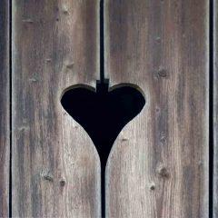 Das ausgeschnittene Herz in der Holztür signalisert geläufig den Zugang zum Plumpsklo.
