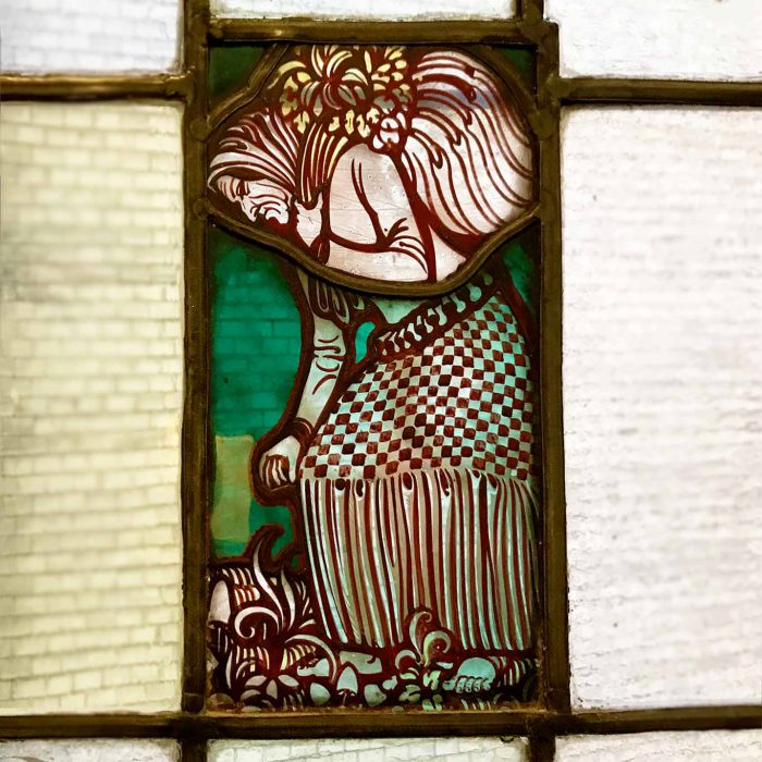 Ein Bleiglasfenster, bemalt mit einer Kräuterhexe im Treppenhaus der Hamburger Dammtorpraxis.