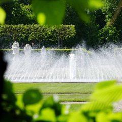 Das Wasserspiel des Glockenbrunnens durch eine Hecke betrachtet.