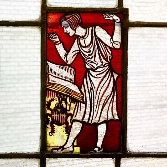 Ein Bildglasfenster im Treppenhaus der Hamburger Dammtorpraxis. Ein Gelehrter liest in einem Buch.