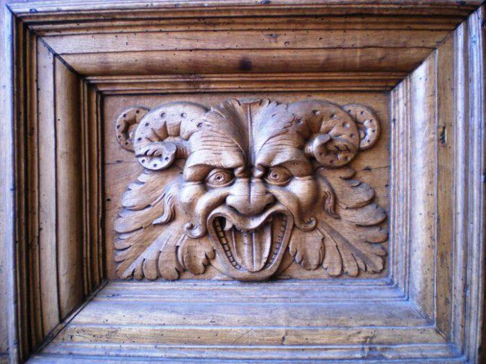 Ein Geisen-oder Bacchuskopf ist in die hölzerne Tür der Basilika zu Assisi geschnitzt.