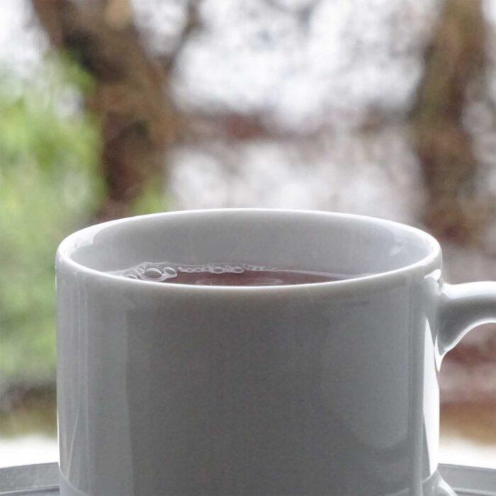 Ein weisser Teepott mit Kräutertee vor natürlichem Hintergrund.